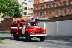 Fire truck rides on an urgent call. Red fire truck rides on an urgent call on city street Royalty Free Stock Image