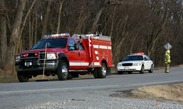 Fire Truck and State Trooper. Two emergency vehicles, a fire truck and a state highway patrol car parked in the roadway at the scene of an accident.  A fireman Stock Photo