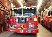 Fire Truck in Station FDNY. Fire trucks in a New York City Fire Department station with equipment and we support our troops sticker across the screen Royalty Free Stock Images