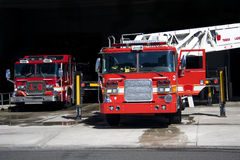 Fire trucks. Two fire trucks parked in the bay with all of the fire fighting equipment and gear ready to go Stock Photo
