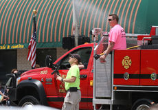Fire trucks with firemen in a  parade in small town America. Fire trucks with firemen with hose spraying in a summer parade in small town America Stock Image