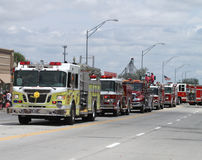 Fire trucks in a  parade in small town America. Fire trucks with lights flashing in a summer parade in small town America Stock Photography