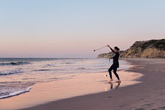 Fire twirler on beach and sunset Royalty Free Stock Images