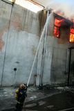 A fire in a warehouse at 108 Frolovska. Kyiv, Ukraine - July 2, 2008: Firefighter extinguishes fire hose supplying water from the ground level. A fire in a Stock Image