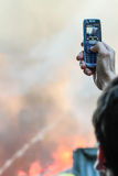 A fire in a warehouse at 108 Frolovska. Kyiv, Ukraine - July 2, 2008: Man using phone shoots video in a fire. A fire in a warehouse at 108 Frolovska (by Iren Royalty Free Stock Photo
