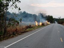 Fire was fired and burnt in agricultural area near local road to destroy dried straw make air and dust pollution. Pm2.5 Thailand smoke global warming outdoor royalty free stock photo