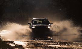 Through fire and water  1. Car is driving through a water-course by high speed Stock Photography