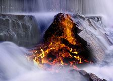 Fire in water. Fire burning and throwing sparks in the midst of a rocky waterfall stock images
