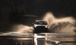 Through fire and water 4. Car is driving through a water-course by high speed Stock Photos