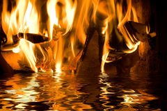 Fire and water. Flames from burning wood reflecting in water Royalty Free Stock Photos