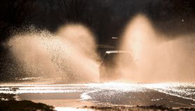 Through fire and water 5. Car is driving through a water-course by high speed Royalty Free Stock Image
