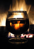 Fire Water. Brandy Glass Lit by fireplace Royalty Free Stock Photo