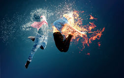 Fire and water collide. Two dancers master fire and water Stock Photography