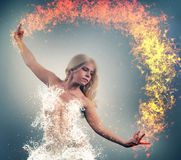 Fire and water. Collide. Woman with water dress is playing with fire Royalty Free Stock Photos
