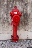 Fire water coming a street hydrant. Red fire water coming a street hydrant near a wall Stock Images