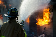 Fire and Water. A fireman pours a stream of water on a burning home stock photos