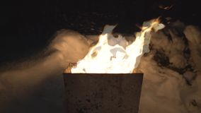 The fire burns in the tank in the wind at night stock footage