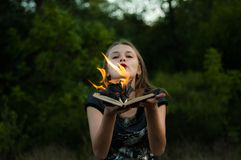A flame over a fire woman, tongues of fire. Flame covered the book. royalty free stock photo