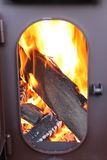 Fire-wood are burning in a fire-chamber of a stove with an opened door Royalty Free Stock Images