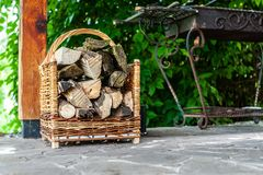 Fire wood pile in wicker basket near the barbecue place, outdoor royalty free stock images