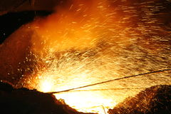 Fire-works. Sparks created when lancing the tap-hole, with the submerged arc furnace structure to the back and heaps of casting sand to the front, at a South Stock Image