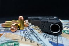 Black firearm and bullets  close-up on a pile of United States currency against a black background. Firearm and bullets on a pile of United States currency  and royalty free stock images