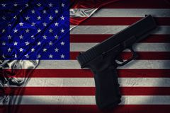 Firearm disposed by diagonal on a United States of America flag. Directly above stock photo