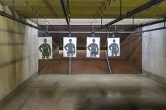 Firearm shooting range wide shot. Indoor Firearm shooting range wide shot with four paper targets royalty free stock photos