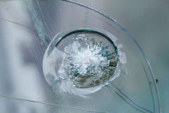 Firearms bullethole on bulletproof glass, cracks background Royalty Free Stock Image
