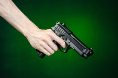 Firearms and murderer topic: human hand holding a gun on a dark green background isolated in studio Royalty Free Stock Photos