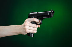Firearms and murderer topic: human hand holding a gun on a dark green background isolated in studio Royalty Free Stock Photography