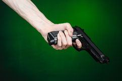 Firearms and murderer topic: human hand holding a gun on a dark green background isolated in studio. Firearms and murderer topic: human hand holding a gun on a Royalty Free Stock Images
