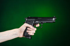 Firearms and murderer topic: human hand holding a gun on a dark green background  in studio Stock Photos