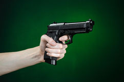 Firearms and murderer topic: human hand holding a gun on a dark green background  in studio Royalty Free Stock Images