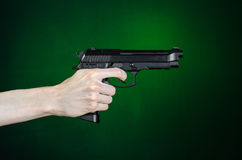 Firearms and murderer topic: human hand holding a gun on a dark green background  in studio Royalty Free Stock Photography