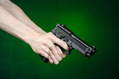 Firearms and murderer topic: human hand holding a gun on a dark green background  in studio Royalty Free Stock Image