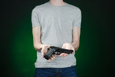 Firearms and murderer topic: man in a gray t-shirt holding a gun on a dark green background isolated in studio Royalty Free Stock Photo