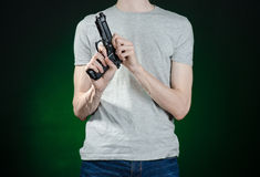 Firearms and murderer topic: man in a gray t-shirt holding a gun on a dark green background isolated in studio Stock Image