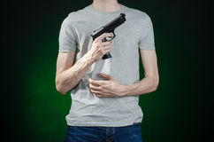 Firearms and murderer topic: man in a gray t-shirt holding a gun on a dark green background isolated in studio Royalty Free Stock Photography