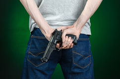 Firearms and murderer topic: man in a gray t-shirt holding a gun on a dark green background isolated in studio Stock Photo