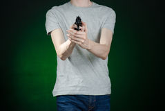 Firearms and murderer topic: man in a gray t-shirt holding a gun on a dark green background isolated in studio Royalty Free Stock Image