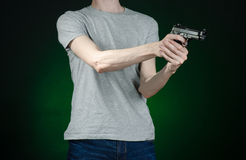 Firearms and murderer topic: man in a gray t-shirt holding a gun on a dark green background isolated in studio Stock Images