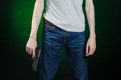 Firearms and murderer topic: man in a gray t-shirt holding a gun on a dark green background isolated in studio Royalty Free Stock Photos