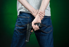 Firearms and murderer topic: man in a gray t-shirt holding a gun on a dark green background  in studio Stock Photo