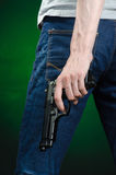 Firearms and murderer topic: man in a gray t-shirt holding a gun on a dark green background  in studio Stock Photography