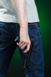Firearms and murderer topic: man in a gray t-shirt holding a gun on a dark green background  in studio Stock Photos