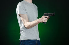 Firearms and murderer topic: man in a gray t-shirt holding a gun on a dark green background  in studio Royalty Free Stock Photo