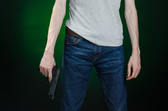 Firearms and murderer topic: man in a gray t-shirt holding a gun on a dark green background  in studio Stock Images