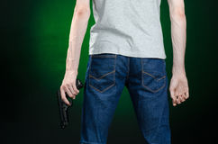Firearms and murderer topic: man in a gray t-shirt holding a gun on a dark green background  in studio Royalty Free Stock Image