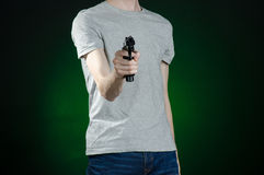 Firearms and murderer topic: man in a gray t-shirt holding a gun on a dark green background  in studio Royalty Free Stock Photography